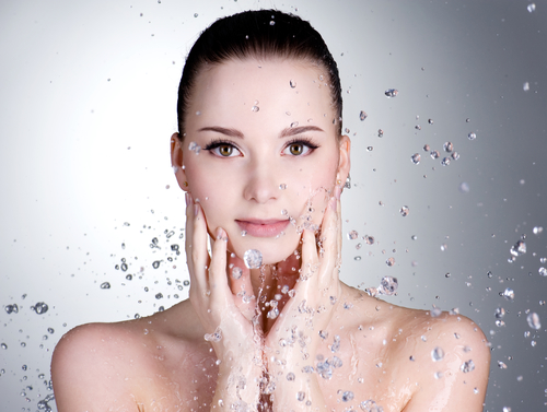 Portrait of beautiful young woman with drops of water around her face